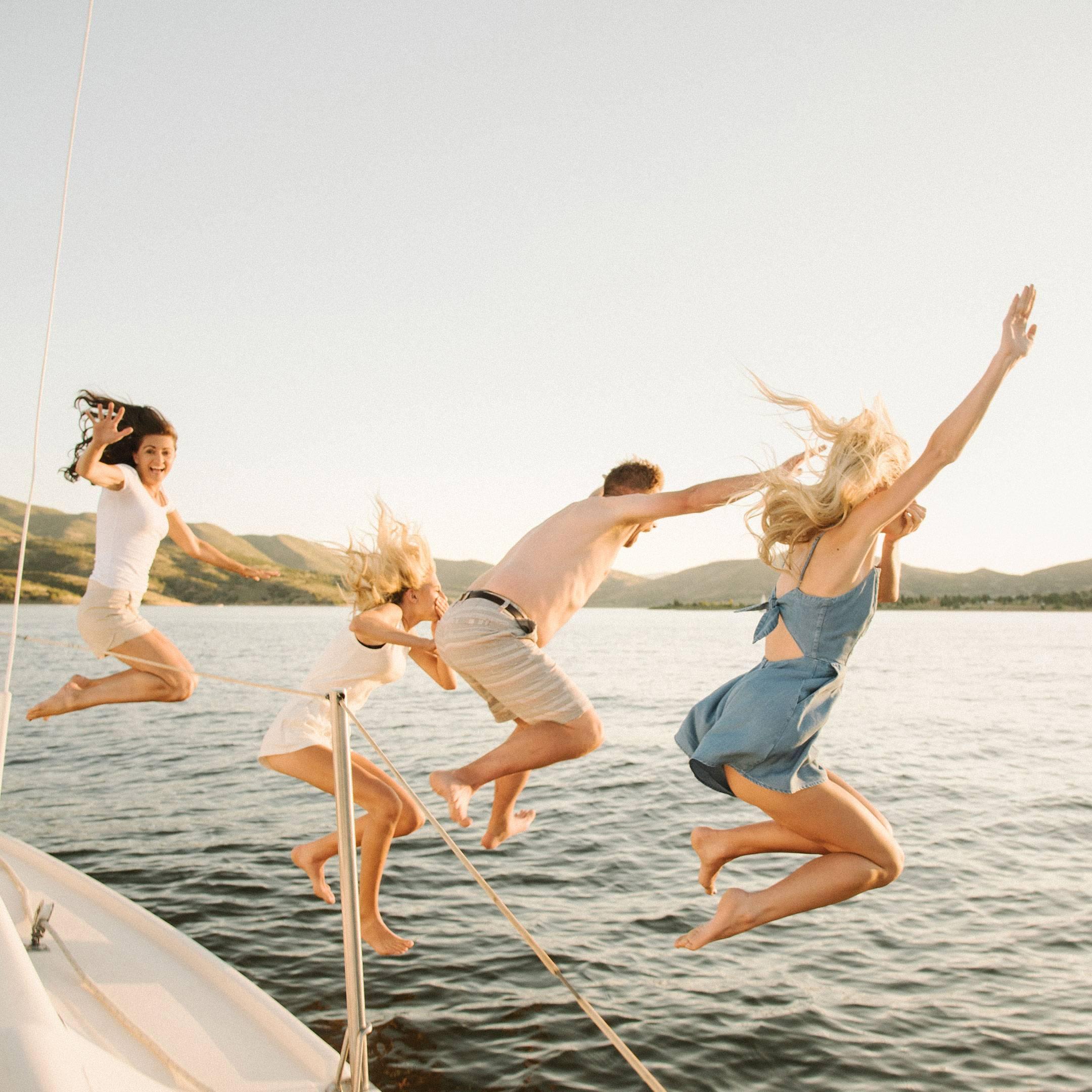 Femmes et hommes qui sautent d'un voilier
