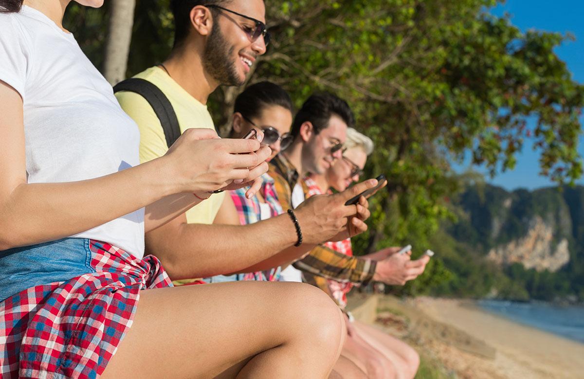 Groupe assis au bord de la plage avec téléphone