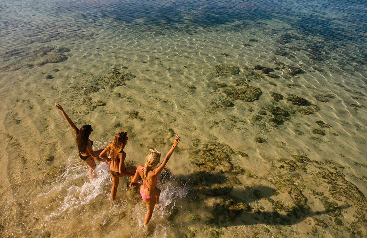 Trois jeunes femmes courent sur la plage