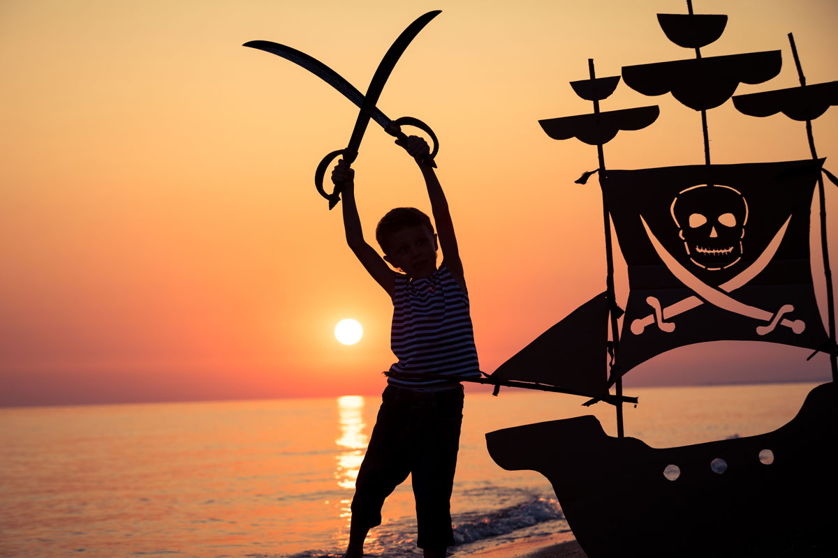 Enfant avec des épées pirates devant un coucher de soleil